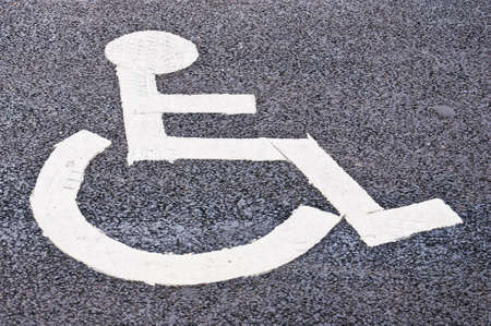 A designated parking spot found in all of the worlds cities that's restricted to all but disabled drivers that have a disability of some sort. photo
