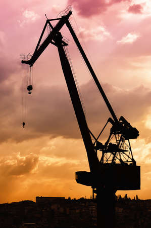 A dockyard crane is silhouetted against a dramatic evening sky. photo