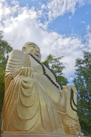 A large golden buddha sits on a hillside overlooking the area of Hua Hin in Thailand. photo