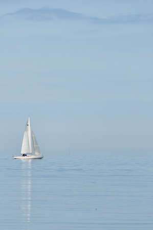 A lone yacht heads out to open sea against a backdrop of a misty island photo