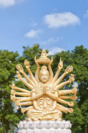 A huge statue of a multi armed buddha sits on a hill near to the city of Hua Hin in Thailand. photo