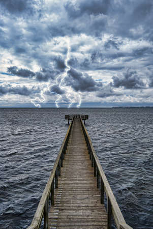 Extreme weather conditions from an approaching storm veiwed from a wooden pier on the coast. photo