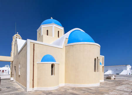 A view of one of the famous blue domed churches from Oia on the greek isle of Santorini. photo