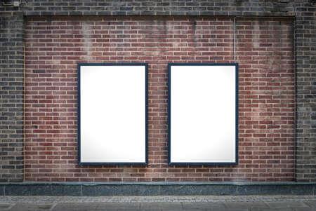 Dos carteles en blanco unido a una pared de ladrillo edificios exteriores.