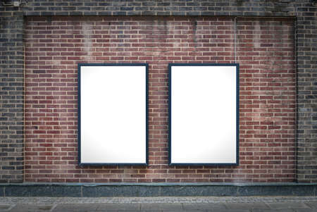 blank poster: Two blank billboards attached to a buildings exterior brick wall. Stock Photo