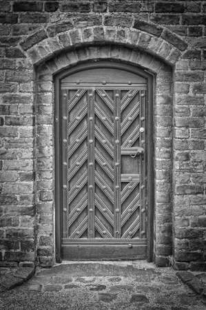 entryway: A black and white photo of an arched doorway to a church.