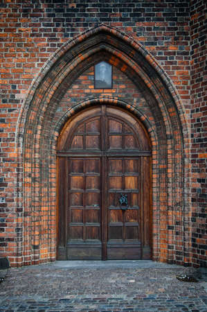 An arched doorway to a gothic style church. photo