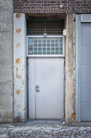 A dirty grungy looking back door leading into an allyway in a typical city.  Stock Photo - 17980962