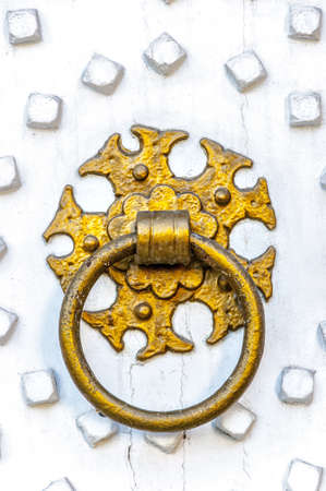 An ornate golden ring knocker on a bright white painted wooden door. photo