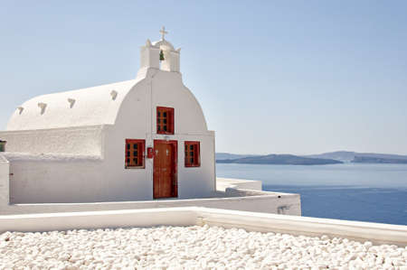 A view of one of the famous churches from Oia on the greek isle of Santorini. photo