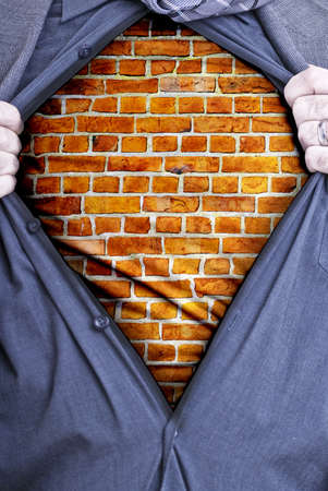 A businessman rips open his shirt and shows how tough he is by revealing a brick wall beneath printed on a t-shirt Stock Photo - 18933284