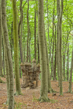 woodland sculpture: A mysterious castle carved out of a dead tree stump in the middle of a woodland area  Stock Photo