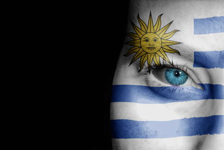 A young female with the flag of Uruguay painted on her face on her way to a sporting event to show her support. Stock Photo