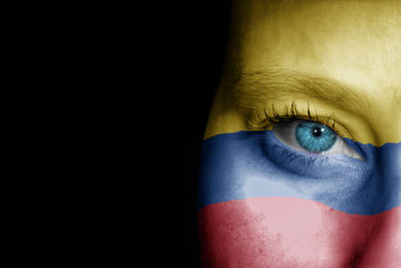 A young female with the flag of Colombia painted on her face on her way to a sporting event to show her support.