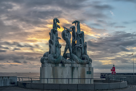 The statue of Hercules fighting the hydra at the Danish harbor of Helsingor at sunrise.