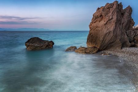Long exposure photograhy at the rocky Kato Petres Beach landscape at dusk. Rhodes, Greece 版權商用圖片