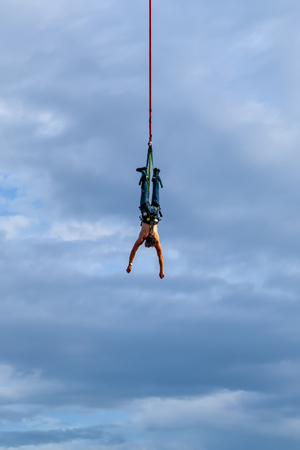 A male action sports thrill seeker jumping from a bungee platform. Фото со стока