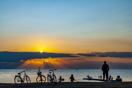 A group of people gather to watch a spectacular sunset at Torekov in Sweden.