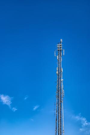 Communications mast set against a blue summer sky Banco de Imagens