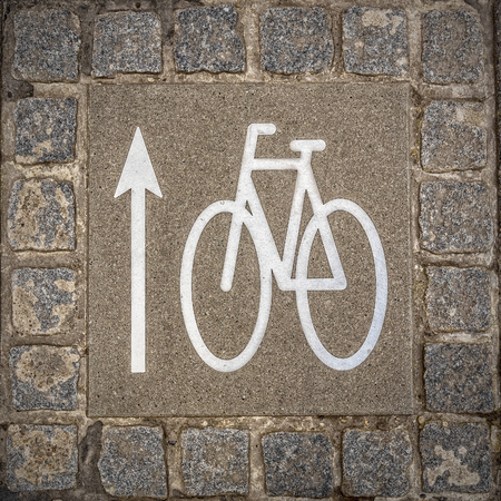 A bicycle lane sign on the ground indicating the direction of travel.