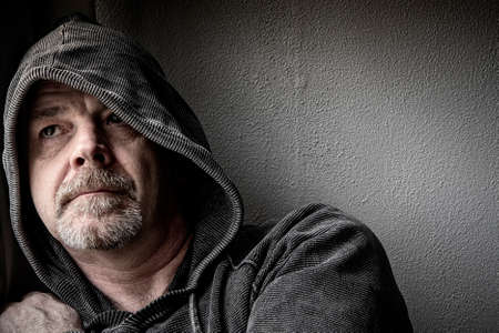 A middle aged man looks to the future for hope whilst in his depression.