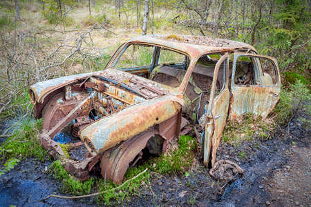 KIRKOE MOSSE, SWEDEN - 30 MAY 2020: A car graveyard situated in a forest at Kirkoe Mosse, Sweden.