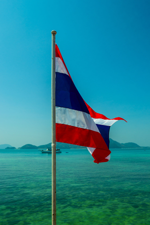 Colorful Thai flag on the picturesque background of the sea with ship. Blue sky on a sunny day. Symbol of Thailand at Cape Panwa, Phuket. Stock Photo