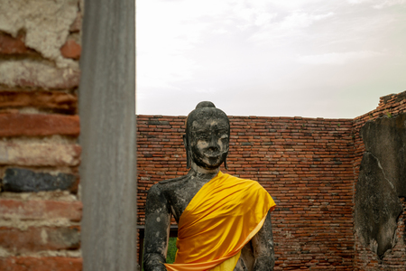 Cropped Sitting Buddha sculpture with golden cassock in Wat Wora Chet Tha Ram Temple, Ayutthaya, Thailand on the brick wall background 版權商用圖片