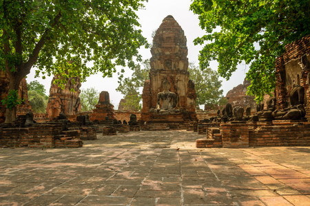 Alley with ancient destroyed Buddha statues, big sculpture and brick pagoda in famous siam temple Wat Mahathat in historical park Ayutthaya, Thailand 免版税图像
