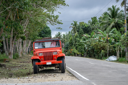 Red retro jeep parked on the roadside of a tropical highway with palm trees in Philippines Stock Photo