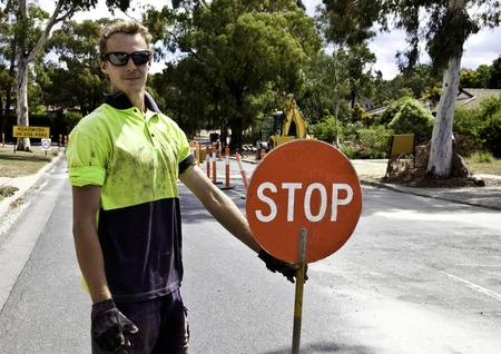 Roadworker controls traffic flow Stock Photo