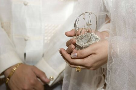 animal pouch: Bride holds wedding coins or Arras pouch