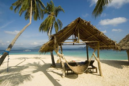Nipa Hut and coconut trees along a white sand beach