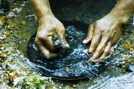 digging: Hands of Gold Panner in the Philippines Stock Photo