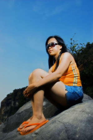 Asian woman on rock by the beach photo