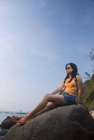 filipina: Asian woman on rock by the beach Stock Photo