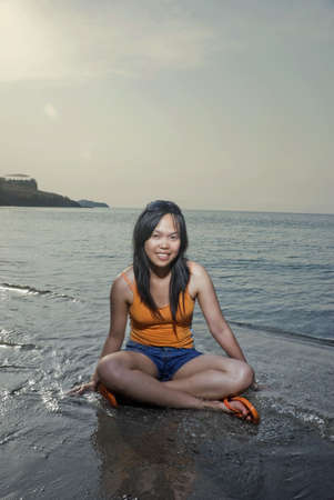 Asian woman sitting on beach photo