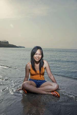 filipina: Asian woman sitting on beach