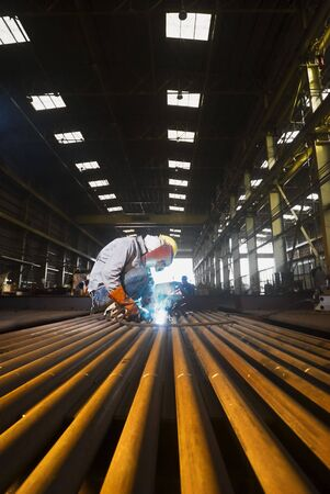 Male welder focused on job at factory