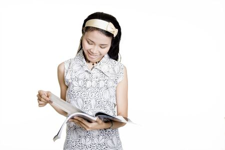 Asian woman reading magazine, against white background photo