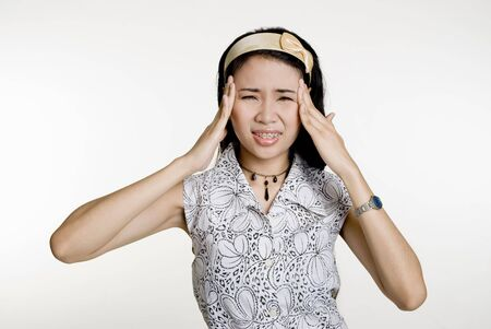 throbbing: Asian woman grimacing in headache pain, against white background
