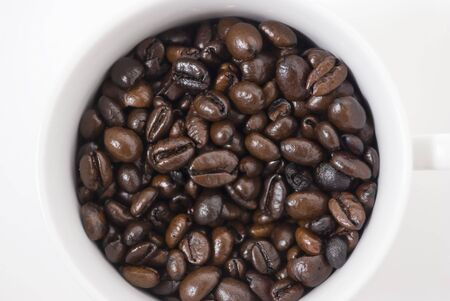 coffeebreak: Closeup shot of coffee beans in cup, shot against white background