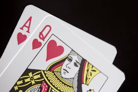 Blackjack cards held by hand against black background