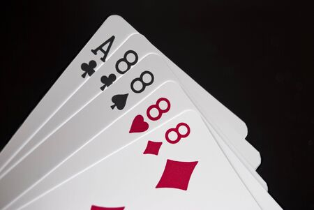 eights: Royal Flush held by hand against black background