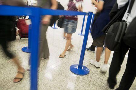 Airline passengers in a queue; queue moves