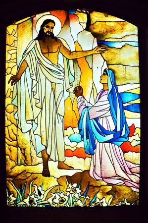 Stained glass depicting a woman praying to Jesus