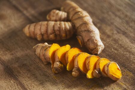 Close-up of turmeric or yellow ginger on chopping board