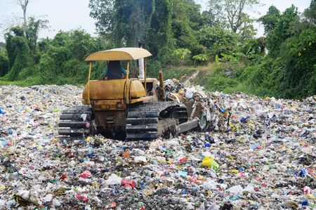 Bulldozer spreads garbage in a landfill; rural area photo