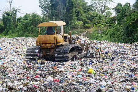 Bulldozer spreads garbage in a landfill; rural area