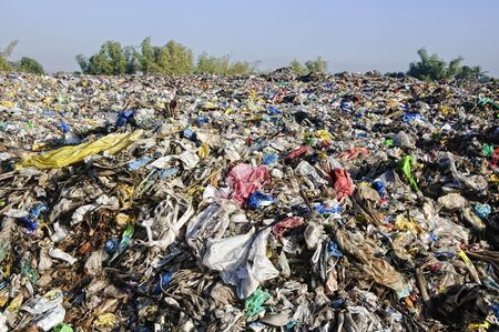 A sea of garbage starts to invade and destroy a beautiful countryside scenery  Stock Photo